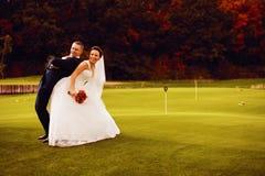 Χαμογελώντας νύφη και νεόνυμφος στον τομέα γκολφ Στοκ φωτογραφίες με δικαίωμα ελεύθερης χρήσης