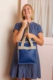 Χαμογελώντας ξανθή γυναίκα με το μπλε πορτοφόλι δέρματος Στοκ Εικόνες