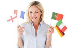 Χαμογελώντας ξανθή γυναίκα που κρατά τις ευρωπαϊκές σημαίες Στοκ εικόνα με δικαίωμα ελεύθερης χρήσης