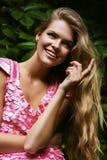 Χαμογελώντας ξανθή γυναίκα στο ρόδινο φόρεμα Στοκ Φωτογραφίες