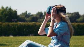 Χαμογελώντας ξανθό κορίτσι που χρησιμοποιεί τα γυαλιά εικονικής πραγματικότητας απόθεμα βίντεο