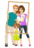 Χαμογελώντας οικογένεια με το γιο, την κόρη και το σκυλί που κοιτάζει μέσω ενός κενού πλαισίου Στοκ Φωτογραφίες