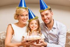 Χαμογελώντας οικογένεια στα μπλε καπέλα με το κέικ Στοκ Φωτογραφία