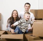 Χαμογελώντας οικογένεια στο παιχνίδι καινούργιων σπιτιών με τα κιβώτια Στοκ Εικόνες