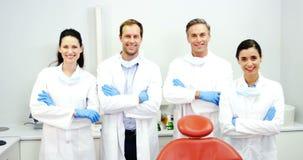 Χαμογελώντας οδοντίατροι που στέκονται με τα όπλα που διασχίζονται απόθεμα βίντεο