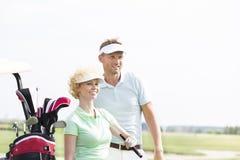 Χαμογελώντας παίκτες γκολφ που στέκονται στο γήπεδο του γκολφ ενάντια στο σαφή ουρανό Στοκ Φωτογραφία