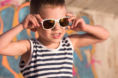 Χαμογελώντας παιδάκι που φορά τα γυαλιά ηλίου και το πουκάμισο ναυτικών στο υπόβαθρο γκράφιτι Στοκ φωτογραφία με δικαίωμα ελεύθερης χρήσης