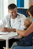 Χαμογελώντας παιδίατρος κατά τη διάρκεια της εργασίας Στοκ Εικόνες