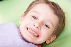 Χαμογελώντας παιδί με το ευτυχές πρόσωπο στην καρέκλα ή το γραφείο οδοντιάτρων Στοκ Εικόνα