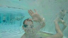 Χαμογελώντας παιδί που κολυμπά με τη διασκέδαση φιλμ μικρού μήκους