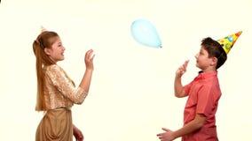 Χαμογελώντας παιδιά που κρατούν τα μπαλόνια και το αγκάλιασμα απόθεμα βίντεο