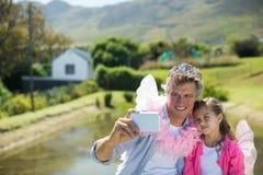 Χαμογελώντας πατέρας και κόρη στο κοστούμι νεράιδων που παίρνει selfie στο κινητό τηλέφωνο στοκ φωτογραφία με δικαίωμα ελεύθερης χρήσης