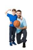 Χαμογελώντας πατέρας και παιδί έτοιμοι να παίξουν την καλαθοσφαίριση Αγόρι που παρουσιάζει δικέφαλους μυς του Στοκ Εικόνα