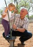Χαμογελώντας πατέρας και το μικρό παιχνίδι κορών του στοκ φωτογραφία με δικαίωμα ελεύθερης χρήσης