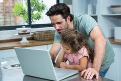 Χαμογελώντας πατέρας που χρησιμοποιεί το lap-top με την κόρη του Στοκ Φωτογραφία