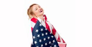 Χαμογελώντας πατριωτική γυναίκα με την Ηνωμένη σημαία Οι ΗΠΑ γιορτάζουν στις 4 Ιουλίου Στοκ Εικόνα