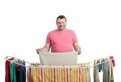 Χαμογελώντας παχύ άτομο στην κόκκινη πλύση ξήρανσης μπλουζών Στοκ εικόνα με δικαίωμα ελεύθερης χρήσης