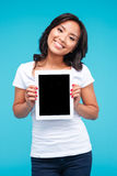 Χαμογελώντας περιστασιακή ασιατική γυναίκα που παρουσιάζει κενή οθόνη υπολογιστή ταμπλετών Στοκ φωτογραφία με δικαίωμα ελεύθερης χρήσης