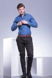 Χαμογελώντας περιστασιακός νεαρός άνδρας που κουμπώνει το πουκάμισό του Στοκ εικόνες με δικαίωμα ελεύθερης χρήσης