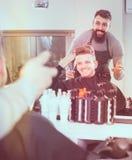 Χαμογελώντας πελάτης που περιγράφει το επιθυμητό κούρεμά του Στοκ Φωτογραφίες