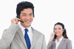 Χαμογελώντας πράκτορας τηλεφωνικών κέντρων με το συνάδελφο πίσω από τον Στοκ Εικόνα