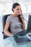 Χαμογελώντας προκλητική επιχειρηματίας που απαντά στο τηλέφωνο Στοκ Φωτογραφία
