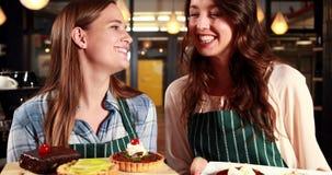 Χαμογελώντας σερβιτόρες που παρουσιάζουν κέικ απόθεμα βίντεο