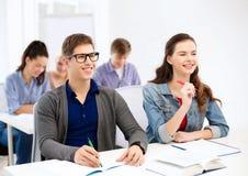 Χαμογελώντας σπουδαστές με τα σημειωματάρια στο σχολείο Στοκ φωτογραφία με δικαίωμα ελεύθερης χρήσης