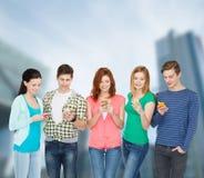 Χαμογελώντας σπουδαστές με τα smartphones Στοκ εικόνες με δικαίωμα ελεύθερης χρήσης