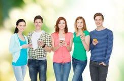 Χαμογελώντας σπουδαστές με τα smartphones Στοκ φωτογραφία με δικαίωμα ελεύθερης χρήσης