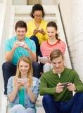 Χαμογελώντας σπουδαστές με smartphone στο σχολείο στοκ εικόνες