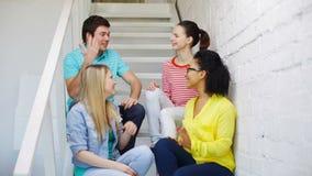 Χαμογελώντας σπουδαστές που κάνουν την υψηλή συνεδρίαση πέντε χειρονομίας απόθεμα βίντεο