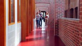 Χαμογελώντας σπουδαστές που περπατούν κάτω από την αίθουσα φιλμ μικρού μήκους