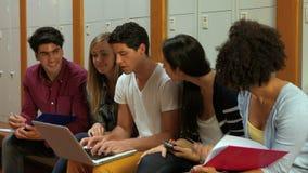 Χαμογελώντας σπουδαστές που χρησιμοποιούν το lap-top στο αποδυτήριο απόθεμα βίντεο