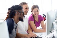 Χαμογελώντας σπουδαστές στην κατηγορία υπολογιστών Στοκ Φωτογραφία