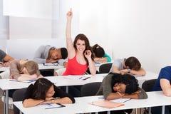 Χαμογελώντας σπουδαστής που αυξάνει το χέρι με τους συμμαθητές που κοιμούνται στο γραφείο Στοκ Εικόνες