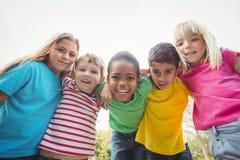 Χαμογελώντας συμμαθητές με τα όπλα το ένα γύρω από το άλλο στοκ εικόνα με δικαίωμα ελεύθερης χρήσης