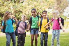 Χαμογελώντας συμμαθητές με τις σχολικές τσάντες σε μια σειρά στοκ φωτογραφίες
