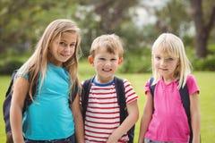 Χαμογελώντας συμμαθητές με τις σχολικές τσάντες στοκ εικόνες