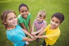 Χαμογελώντας συμμαθητές που βάζουν τα χέρια από κοινού στοκ εικόνες