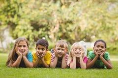 Χαμογελώντας συμμαθητές που βρίσκονται σε μια σειρά στη χλόη στοκ φωτογραφίες με δικαίωμα ελεύθερης χρήσης