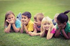 Χαμογελώντας συμμαθητές που βρίσκονται σε μια σειρά στη χλόη στοκ εικόνες