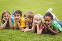 Χαμογελώντας συμμαθητές που βρίσκονται σε μια σειρά στη χλόη στοκ εικόνες με δικαίωμα ελεύθερης χρήσης