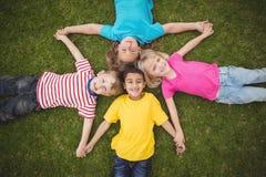 Χαμογελώντας συμμαθητές που βρίσκονται στη χλόη και το κράτημα των χεριών στοκ εικόνες