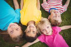 Χαμογελώντας συμμαθητές που βρίσκονται στη χλόη στοκ εικόνα