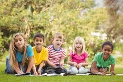 Χαμογελώντας συμμαθητές που κάθονται στη χλόη και τη μελέτη στοκ εικόνες