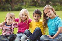 Χαμογελώντας συμμαθητές που κάθονται στη χλόη στοκ φωτογραφία με δικαίωμα ελεύθερης χρήσης