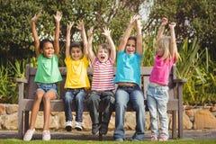 Χαμογελώντας συμμαθητές που κάθονται στον πάγκο και ενθαρρυντικοί στοκ εικόνα με δικαίωμα ελεύθερης χρήσης