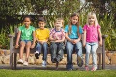 Χαμογελώντας συμμαθητές που κάθονται στον πάγκο στοκ εικόνες