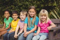 Χαμογελώντας συμμαθητές που κάθονται στον πάγκο στοκ φωτογραφίες με δικαίωμα ελεύθερης χρήσης